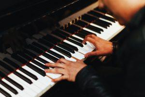 man plays yamaha piano